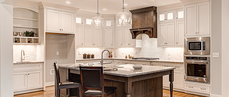 Country kitchen with large hood and granite counters